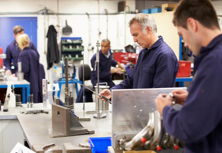 pracownicy w fabryce optymalizują produkcję